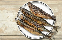 Grilled Mackerel fish on a white plate. Fatty, oily fish is an excellent and healthy source of DHA and EPA, which are two key types of omega-3 acid.