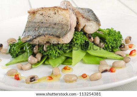 Grilled Mackerel - Pan fried fresh mackerel fillet on a bed of green vegetables and black eyed beans, drizzled with red chilli, lime and olive oil dressing.