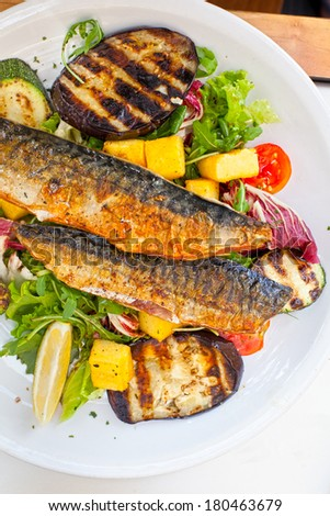 grilled mackerel with roasted vegetables served on plate in restaurant