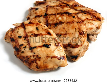 Grilled marinaded and herbed chicken breasts on a white plate.