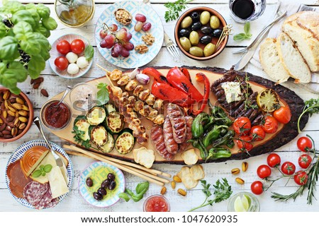 Grilled meat, chicken skewers and sausage  with roasted vegetables and appetizers variety serving on party outdoor table. Mediterranean dinner table concept. Overhead view.