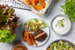 Grilled meat free plant based cutlets with sweet potato wedges, green mix salad and white sauce on gray table. Healthy vegan or vegetarian food concept. Top view.