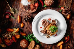 grilled meat medallions with stewed potatoes, mushrooms and white sauce on white plate on wooden background in beautiful composition among vegetables and spices. Top view. Flat lay