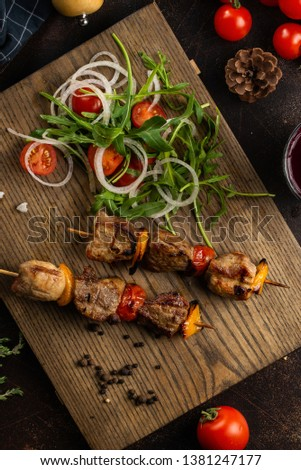 Grilled meat skewers on wooden board with vegetable salad– stock image #1381247177