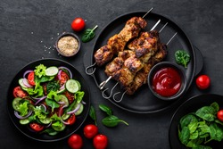 Grilled meat skewers, shish kebab and healthy vegetable salad of fresh tomato, cucumber, onion, spinach, lettuce and sesame on black background, top view