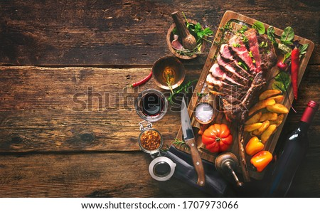 Grilled meat, sliced tomahawk beef steak with spices, french fries and vegetables on a rustic background