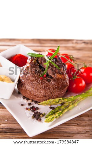 Grilled meat with fresh vegetable on wooden table #179584847