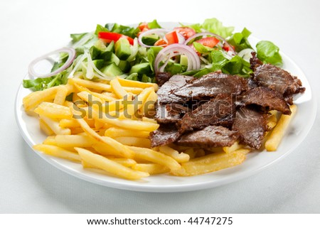 Grilled meat with fried potatoes and vegetable salad