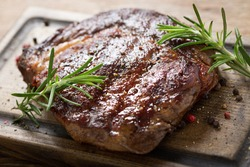grilled meat with rosemary on a wooden board