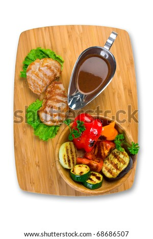 Grilled meat with tomato sauce and vegetables isolated on a white background