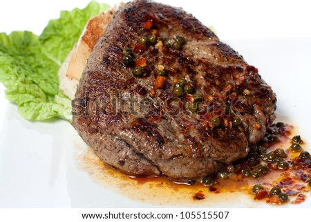 Grilled meat with vegetable sauce. White bread and green salad