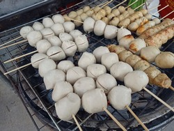 Grilled meatballs in bamboo skewers on gridiron and stove with selective focus and blurred background.A street food is one of the most popular in Thailand.