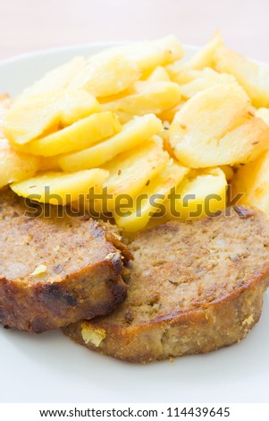 Grilled meatloaf with roasted potatoes selective focus on the meat