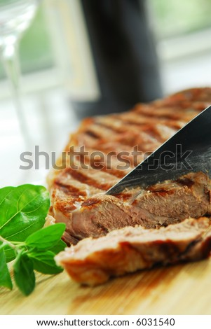 Grilled New York steak being cut on a cutting board