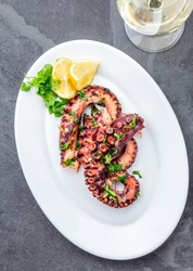 Grilled octopus on white plate served with white wine , top view. Seafood.