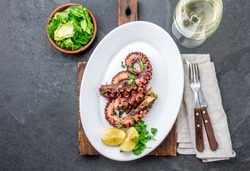 Grilled octopus on white plate serverd with white wine , top view. Seafood.
