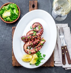 Grilled octopus on white plate with white wine. greek food