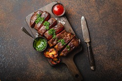 Grilled or fried and sliced marbled meat steak with fork, tomatoes as a side dish and different sauces on wooden cutting board, top view, close-up, stone rustic background. Beef meat steak concept