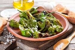Grilled padron peppers with salt and and olive oil on plate. Pimientos de Padron.
