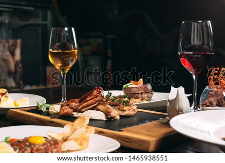 Grilled partridge, sea bass, Tartarus.  Different dishes on the table in the restaurant. Photo stock ©