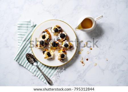 Grilled peaches topped with whipped cream, blackberries and honey drizzle on gold-rimmed plate.