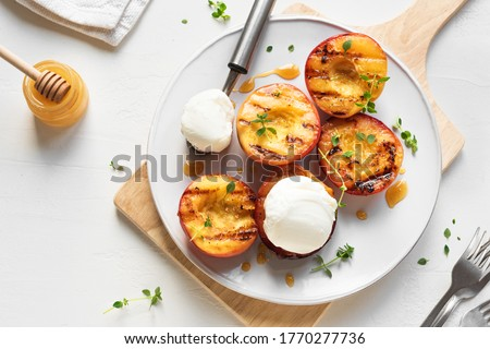 Grilled Peaches with Thyme, Honey and scoop of Vanilla Ice Cream on white plate, top view, copy space. Homemade bbq roasted peaches or nectarines, rustic summer dessert.