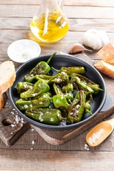 Grilled pepper Padron in a frying pan on a wooden table. Spanish cuisine. Pimientos de Padron