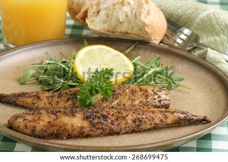 grilled peppered  mackerel fillets wit lemon and baby rocket leaves