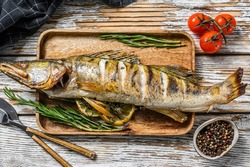 Grilled pike perch, pikeperch fish. White wooden background. Top view