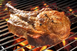 Grilled pork chop on flaming grill.
