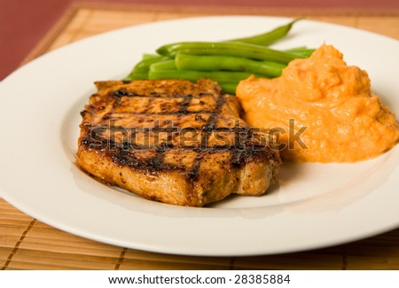 Grilled pork chop served with green beans and mashed sweet potatoes