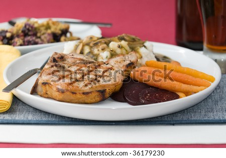Grilled pork chop with mashed potatoes, vegetables, mushroom gravy and beer