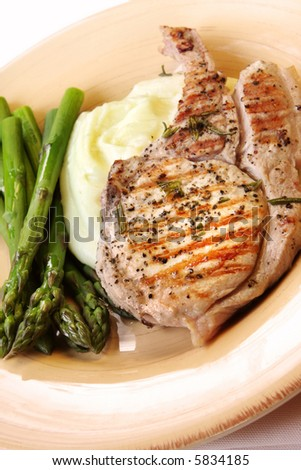 Grilled pork chop with potato mash and fresh asparagus. - stock photo