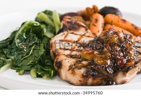 Grilled pork chop with roasted vegetables, swiss chard, and balsamic vinegar and cherry sauce