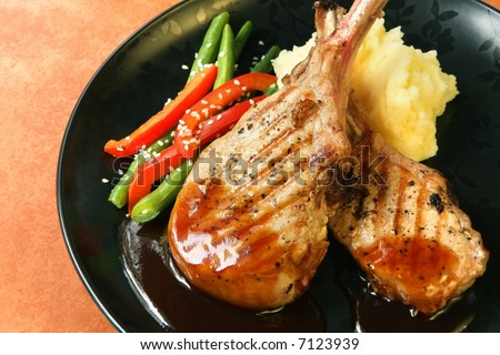 Grilled pork chops with mashed potato, green beans and red capsicum, topped with barbecue sauce.