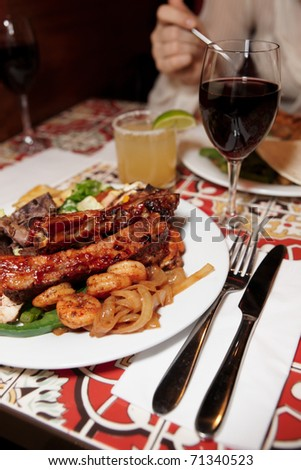 Grilled pork ribs and shrimps with cocktail and wine - perfect dinner - stock photo