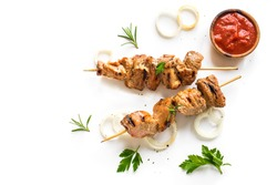 Grilled pork skewers isolated on white background, top view. Meat pork, chicken or turkey shish kebab with tomato sauce,  herbs and spices.