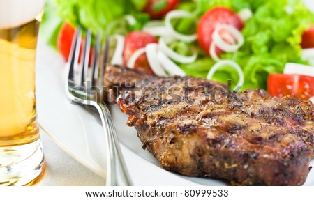 Grilled pork steak and a glass of bear