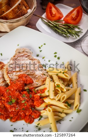 Grilled pork steak meat with tomato sauce and pasta