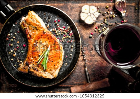 Grilled pork steak with red wine. On wooden background.