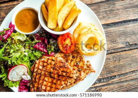 Grilled pork steak with vegetables salad and french fries #571186990