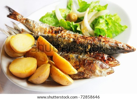Grilled portugal sardine fish served with green salad and potatoes