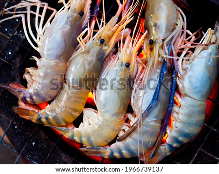 Grilled prawn on flaming grill. Close-up row of raw river prawns are being grilled on the grille on charcoal. Foto stock ©