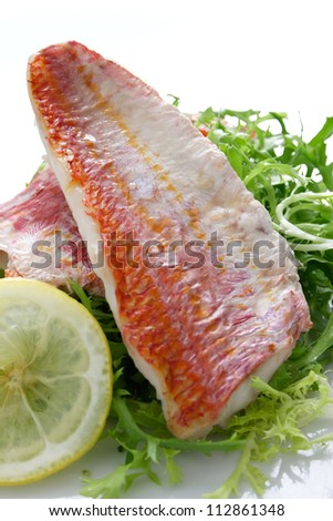Grilled red snapper resting over a bed of greens and a slice of lemon.