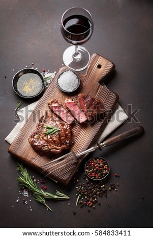 Grilled ribeye beef steak with red wine, herbs and spices. Top view #584833411