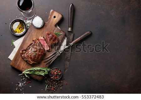 Grilled ribeye beef steak with red wine, herbs and spices. Top view with copy space for your text #553372483