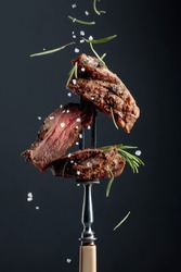 Grilled ribeye beef steak with rosemary on a black background. Beef steak on a fork sprinkled with rosemary and sea salt.