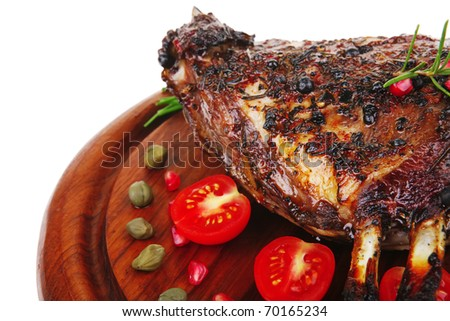 grilled ribs with tomatoes and capers on wooden plate isolated over  white background . shallow dof