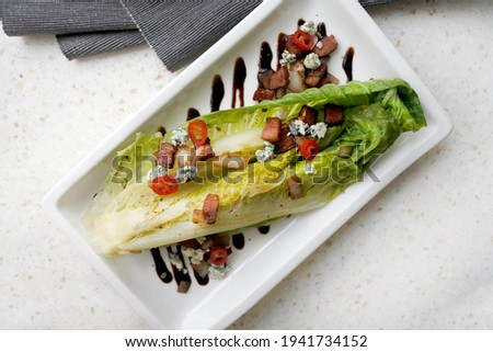 Grilled Romaine Lettuce warm salad with bacon, blue cheese and onion dressing with  balsamic vinegar sauce. On a white square plate on a gray tablecloth. Close-up. Copy space. Horizontal top view. Photo stock ©