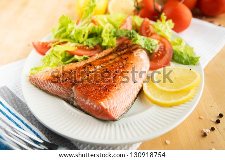 Grilled Salmon Fillet Served with Tomatoes and Romaine Salad - stock photo